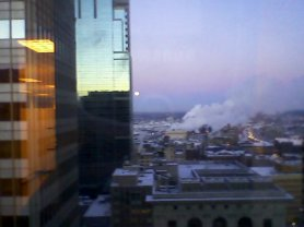 Moon falling in the west and sunrise reflected in the glass towers facing east...amazing. This is from my office window. Straight ahead was new Twins' stadium construction.